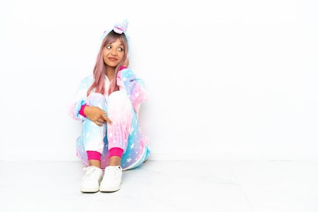 Молодая женщина смешанной расы в пижаме с единорогом сидит на полу на белом фоне, думая об идее