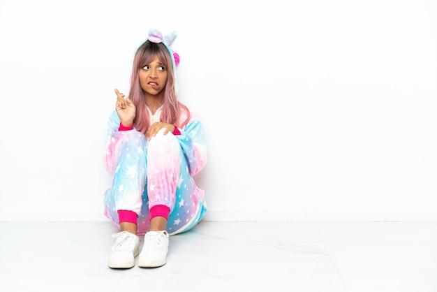 Молодая женщина смешанной расы в пижаме с единорогом сидит на полу на белом фоне со скрещенными пальцами и желает всего наилучшего