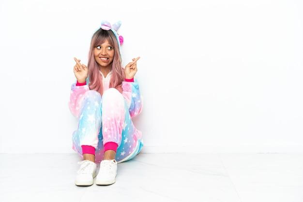 指を交差させて白い背景で隔離の床に座っているユニコーンのパジャマを着て若い混血の女性