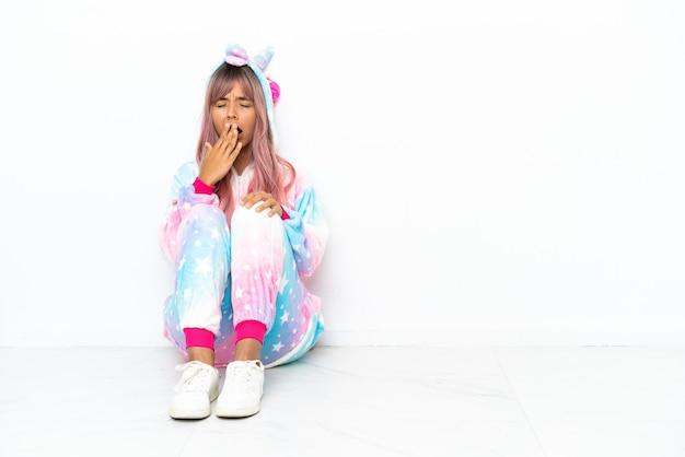 Молодая женщина смешанной расы в пижаме с единорогом сидит на полу на белом фоне, зевая и прикрывая широко открытый рот рукой