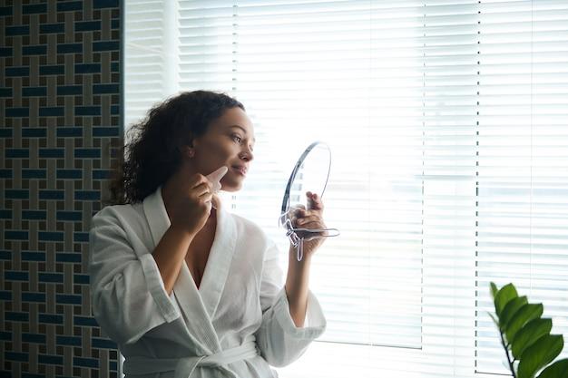 흰색 와플 목욕 가운을 입은 젊은 혼혈 여성은 뺨에 옥 구아샤 마사지기를 사용하고, 배경에 창문이 있는 욕실에 서서 거울 반사를 바라보고 있습니다.