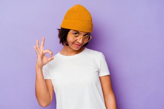 보라색 배경 명랑 하 고 확신 보여주는 확인 제스처에 고립 된 모직 모자를 쓰고 젊은 혼합 된 인종 여자.