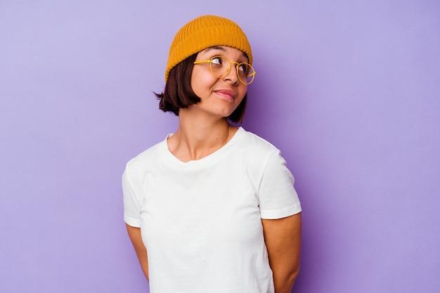 目標と目的を達成することを夢見ている紫色の背景に分離されたウールのキャップを身に着けている若い混血の女性