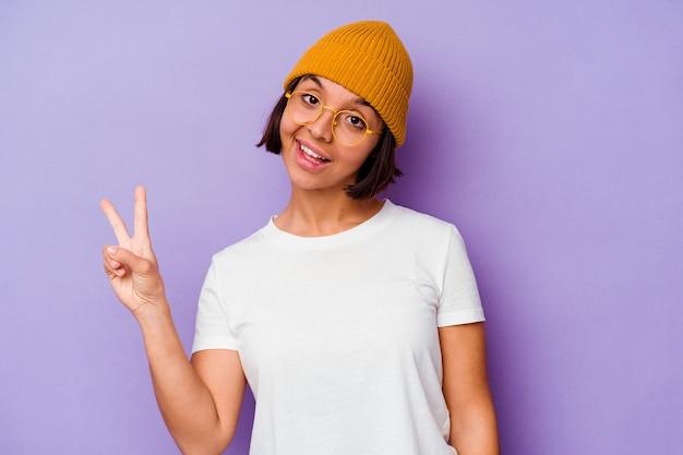 紫色の背景に分離されたウールのキャップを身に着けている若い混血の女性は、指で平和のシンボルを示して楽しくてのんき。