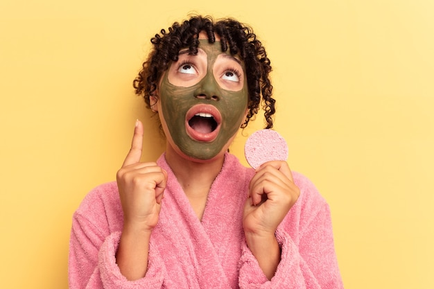 Young mixed race woman wearing a bathrobe holding a make-up remover sponge isolated on yellow background pointing upside with opened mouth.