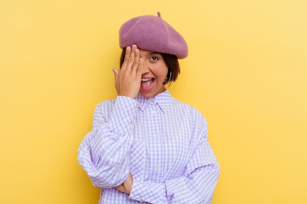 Young mixed race woman wearing a beret isolated on yellow background having fun covering half of face with palm.