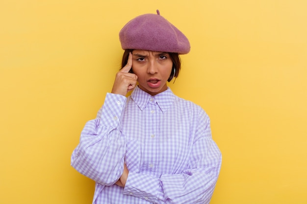 Young mixed race woman wearing a beret isolated on yellow background pointing temple with finger, thinking, focused on a task.