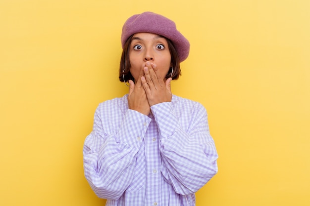 Young mixed race woman wearing a beret isolated on yellow wall shocked covering mouth with hands.