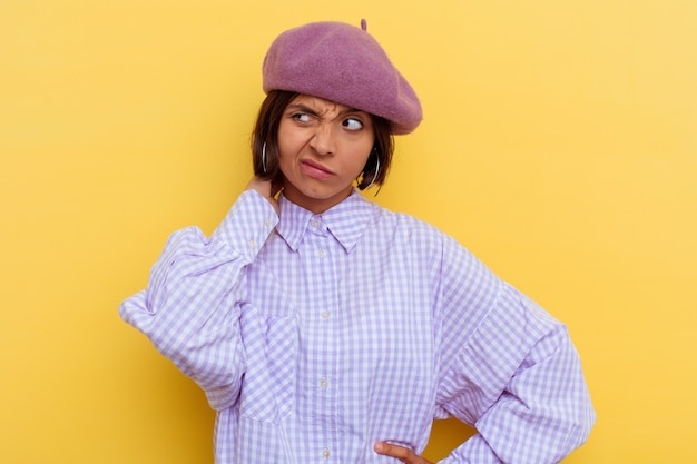 Young mixed race woman wearing a beret isolated on yellow wall suffering neck pain due to sedentary lifestyle.