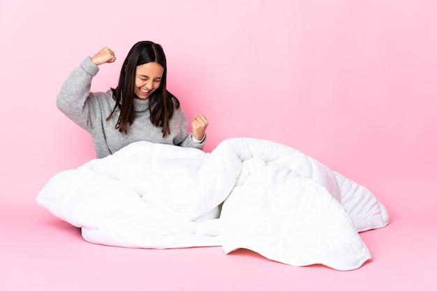 Молодая женщина смешанной расы в пижаме сидит на полу и празднует победу