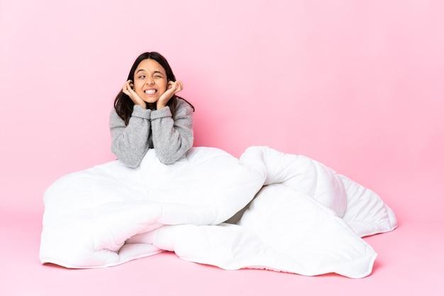 欲求不満と耳を覆う床に座ってパジャマを着ている若い混血の女性