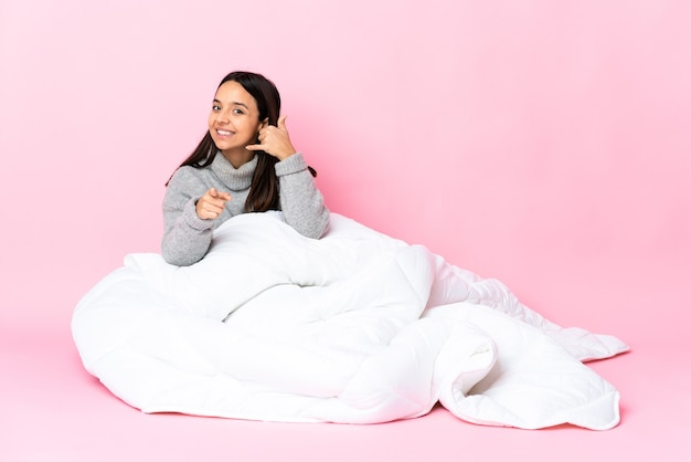 Молодая женщина смешанной расы в пижаме сидит на полу, делая жест по телефону и указывая вперед