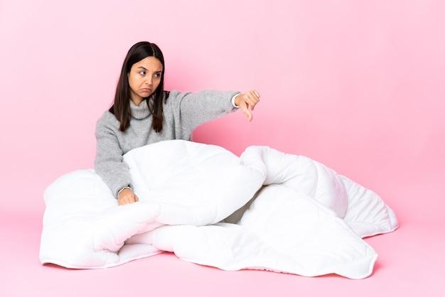 床に座ってパジャマを着ている若い混血の女性
