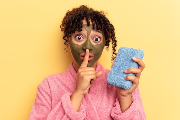 Young mixed race woman wearing a pink bathrobe holding a shower sponge isolated on yellow background keeping a secret or asking for silence.