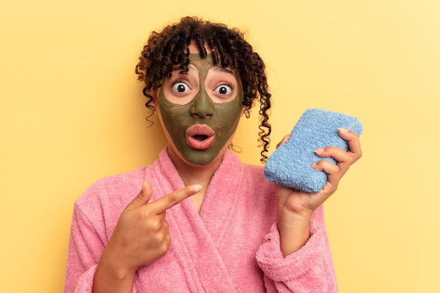 Young mixed race woman wearing a pink bathrobe holding a shower sponge isolated on yellow background pointing to the side