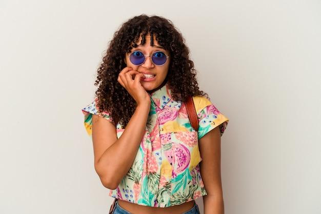 休暇を取るサングラスをかけている若い混血の女性は、神経質で非常に心配して、爪を噛んで孤立しました。