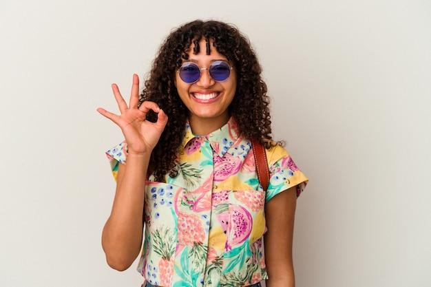 サングラスをかけて休暇を取っている若い混血の女性は、陽気で自信を持って大丈夫なジェスチャーを示しています。