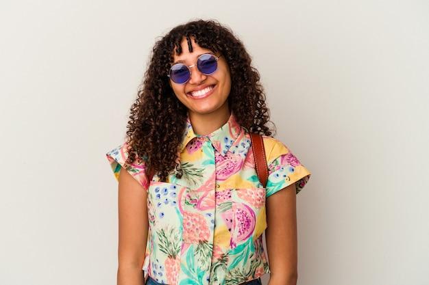 休暇を取るサングラスをかけている若い混血の女性は、幸せ、笑顔、そして陽気に孤立しました。