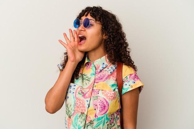 サングラスをかけた若い混血の女性が休暇を取って孤立し、開いた口の近くで叫び、手のひらを握っていた。