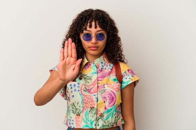 サングラスをかけた若い混血の女性は、一時停止の標識を示して、あなたを防ぐために伸ばした手で立って孤立した休暇を取ります。