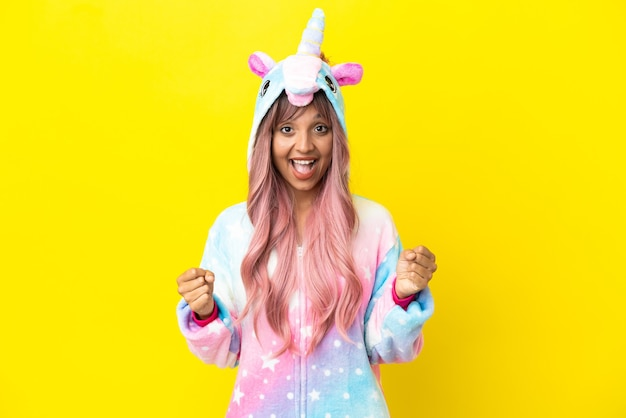 Young mixed race woman wearing a unicorn pajama isolated on white background celebrating a victory in winner position
