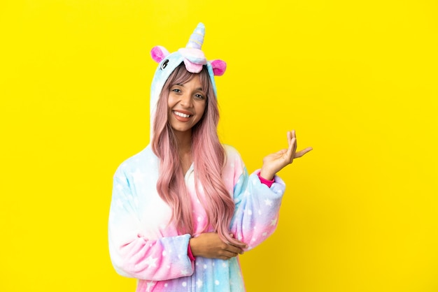 Young mixed race woman wearing a unicorn pajama isolated on white background extending hands to the side for inviting to come