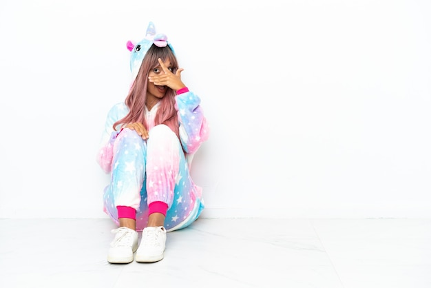 Young mixed race woman wearing a unicorn pajama sitting on the floor isolated on white background covering eyes by hands and smiling
