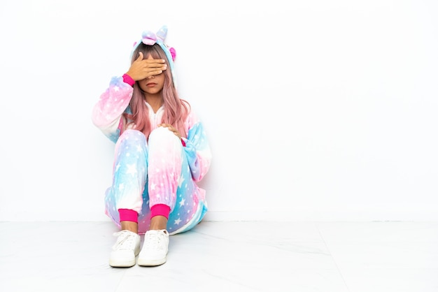Young mixed race woman wearing a unicorn pajama sitting on the floor isolated on white background covering eyes by hands. do not want to see something
