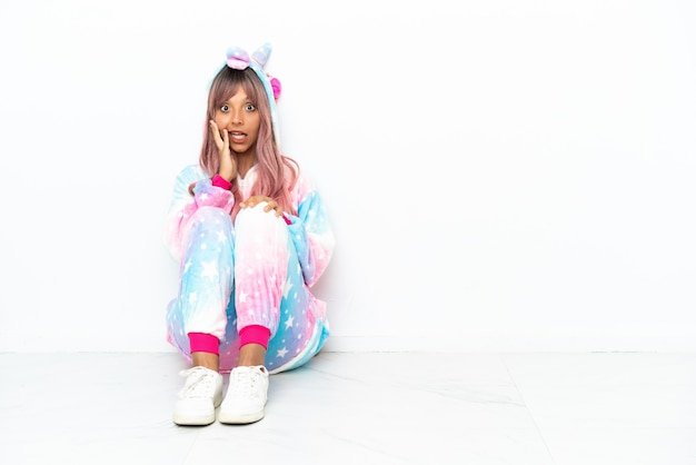 Young mixed race woman wearing a unicorn pajama sitting on the floor isolated on white background with surprise and shocked facial expression