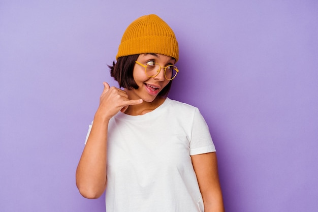 Young mixed race woman wearing a wool cap isolated on purple background showing a mobile phone call gesture with fingers.