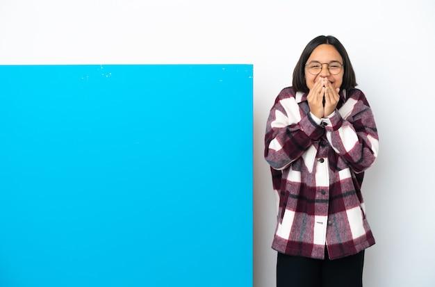 큰 파란색 현수막을 가진 젊은 혼합 된 인종 여자는 행복하고 손으로 입을 덮고 웃고 격리