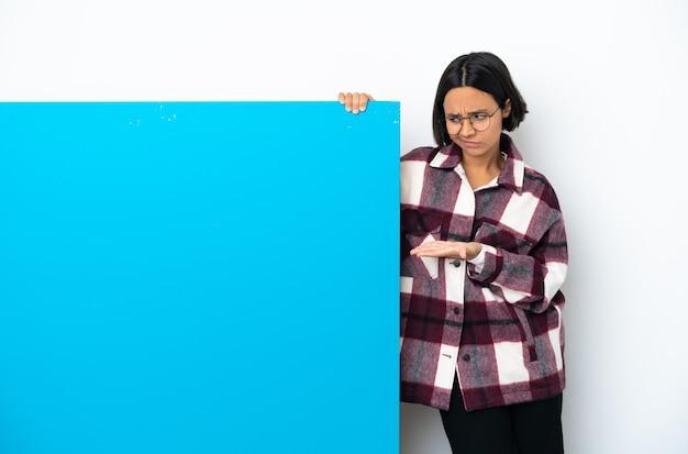 의심과 copyspace를 들고 고립 된 큰 파란색 현수막을 가진 젊은 혼혈 여자