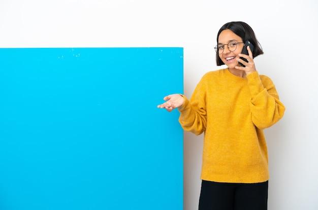누군가와 휴대 전화로 대화를 유지하는 고립 된 큰 파란색 현수막을 가진 젊은 혼혈 여자