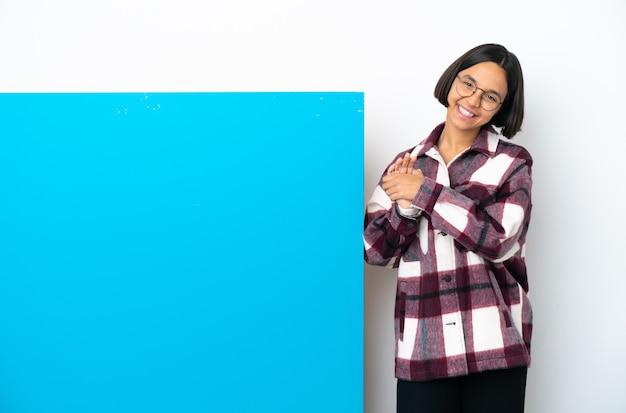 박수 흰색 배경에 고립 된 큰 파란색 현수막을 가진 젊은 혼혈 여성