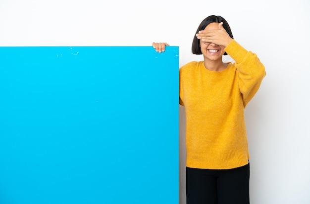 手で目を覆い、笑顔の白い背景で隔離の大きな青いプラカードを持つ若い混血の女性