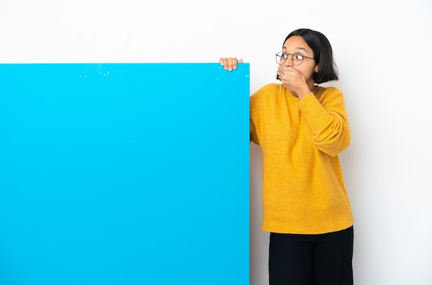 Молодая женщина смешанной расы с большим синим плакатом на белом фоне, закрывающим рот и смотрящим в сторону