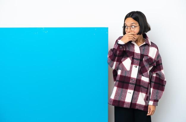 側を見ながら驚きのジェスチャーをしている白い背景に分離された大きな青いプラカードを持つ若い混血女性