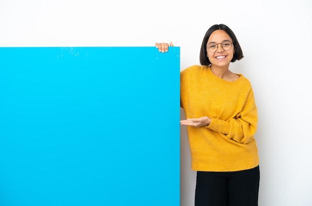 白い背景に大きな青いプラカードを持つ若い混血の女性が、来るように誘うために手を横に伸ばす