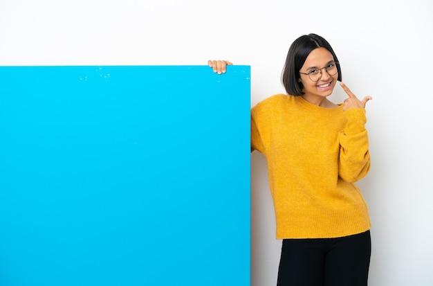 親指を立てるジェスチャーを与える白い背景で隔離の大きな青いプラカードを持つ若い混血の女性