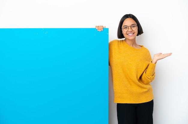 広告を挿入するために手のひらに架空のコピースペースを保持している白い背景で隔離の大きな青いプラカードを持つ若い混血の女性
