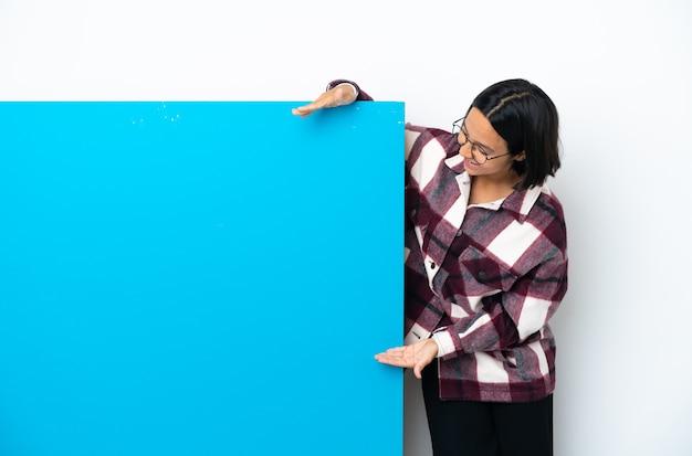광고를 삽입하는 copyspace를 들고 흰색 배경에 고립 된 큰 파란색 현수막을 가진 젊은 혼혈 여자
