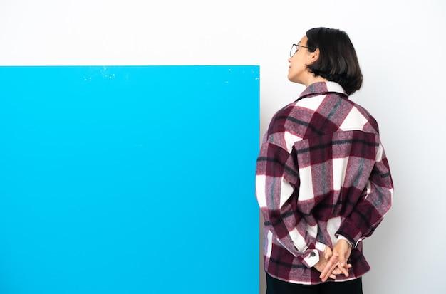 Молодая женщина смешанной расы с большим синим плакатом, изолированным на белом фоне в заднем положении и оглядываясь назад
