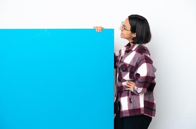 Молодая женщина смешанной расы с большим синим плакатом на белом фоне в боковом положении