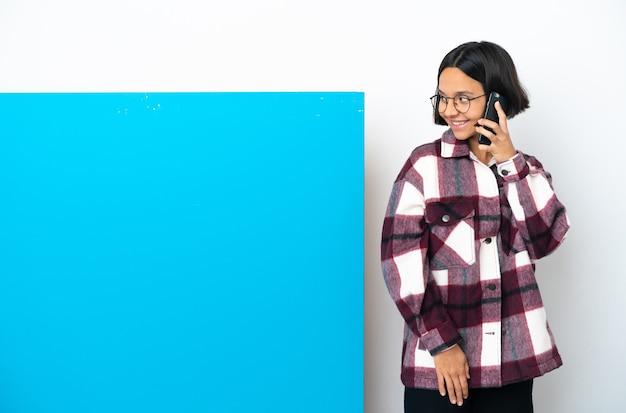 Молодая женщина смешанной расы с большим синим плакатом на белом фоне разговаривает с кем-то по мобильному телефону