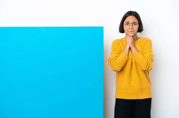 흰색 배경 웃음에 고립 된 큰 파란색 현수막을 가진 젊은 혼혈 여자