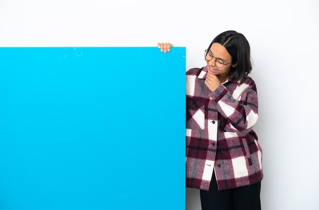 Молодая женщина смешанной расы с большим синим плакатом на белом фоне смотрит в сторону и улыбается