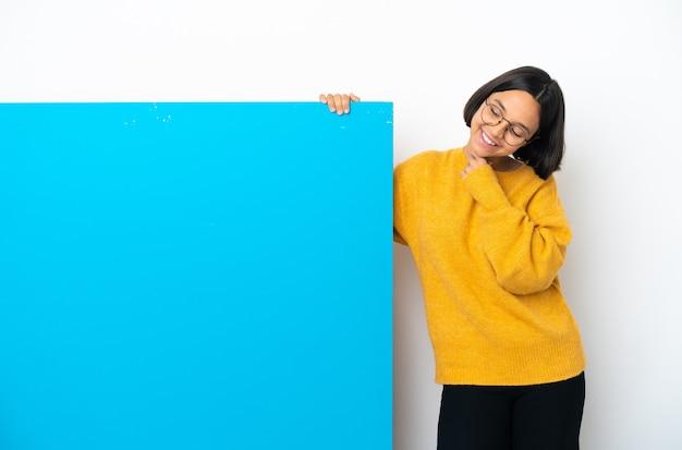 Молодая женщина смешанной расы с большим синим плакатом на белом фоне смотрит вверх, улыбаясь