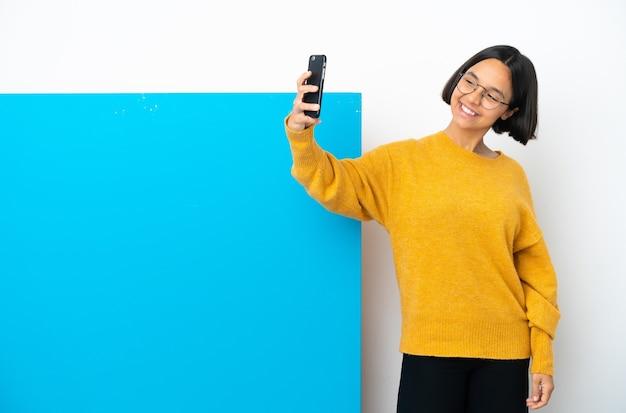 Молодая женщина смешанной расы с большим синим плакатом на белом фоне делает селфи