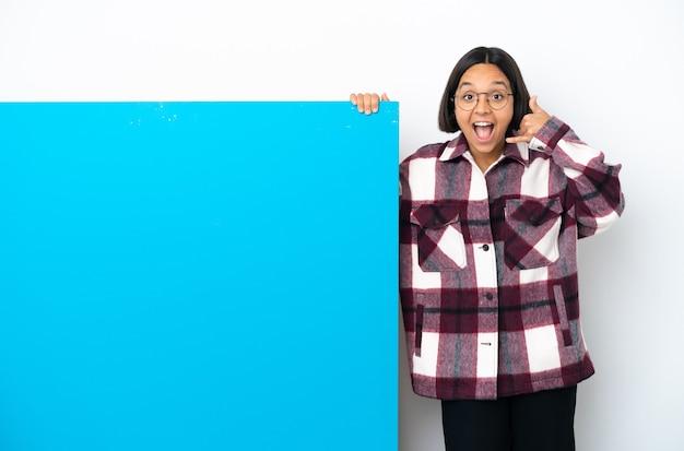 Молодая женщина смешанной расы с большим синим плакатом на белом фоне, делая жест по телефону и сомневаясь