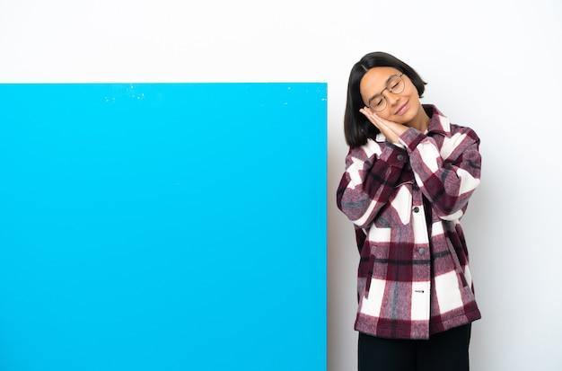 Dorable 표현에서 수면 제스처를 만드는 흰색 배경에 고립 된 큰 파란색 현수막을 가진 젊은 혼합 된 인종 여자